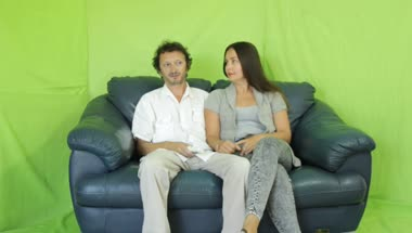 Couple watching tv on their sofa against a green screen绿布抠像素材